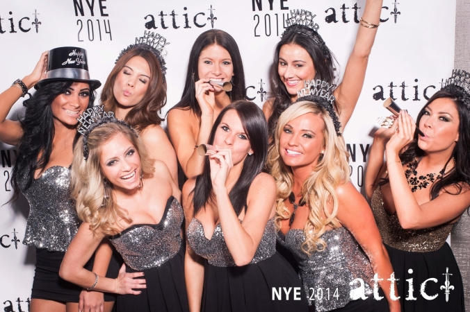 lovely hostesses pose on the step and repeat background for New Years Eve 2014 party at the Attic