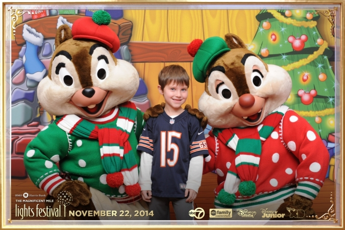 Chip and Dale pose with young fan on the step and repeat background, Magnificent Mile Festival of Lights Parade 2014