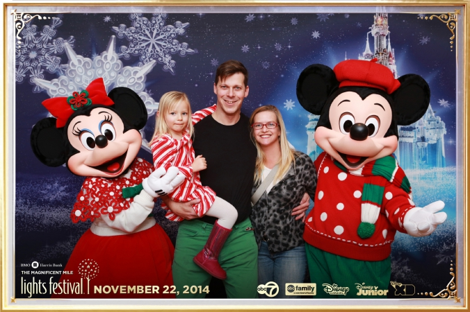 Handsome family poses with Mickey and Minnie Mouse at abc7 Disney character meet and greet, festival of lights, downtown chicago