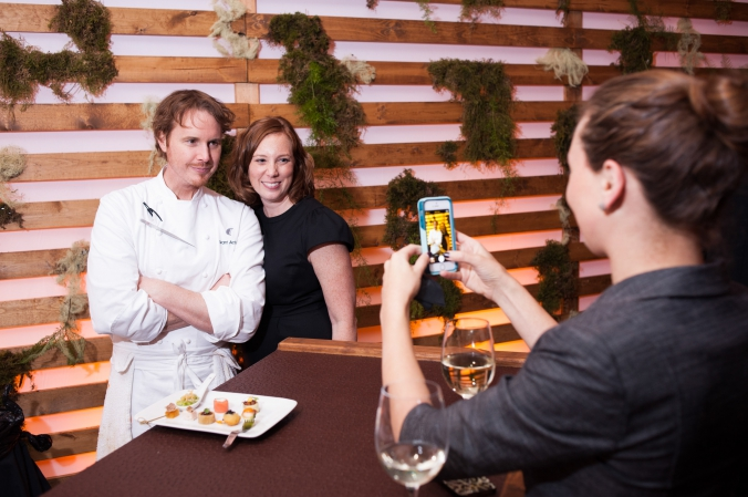 Grant Achatz poses wtih guest at private celebrity chef event in downtown chicago.