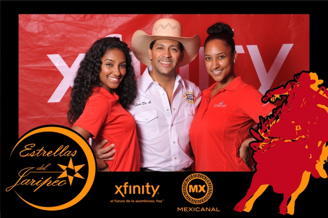 star of estrellas del jaripeo poses with two lovely ladies for xfinity mexicanal step repeat photo activity with onsite photo printing