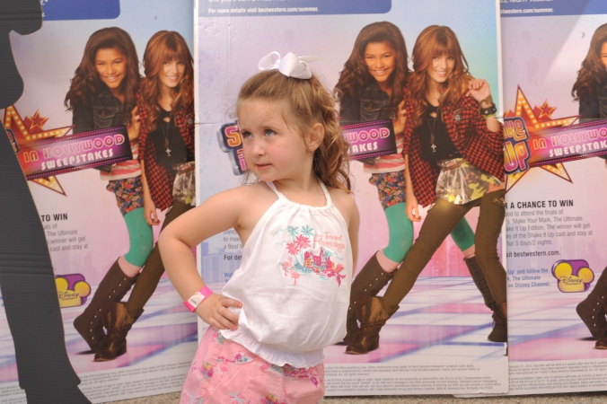 young girl poses with attitude on the step and repeat, disney tv show promotion at mall